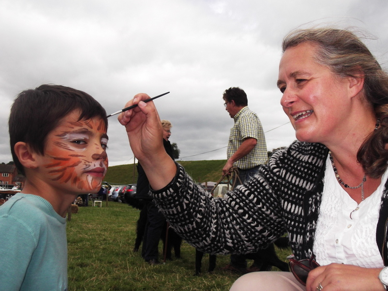 Louise facepainting Tom into a tiger at the Lindridge show, August 2014